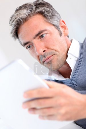 40-year-old man at home using electronic tablet
