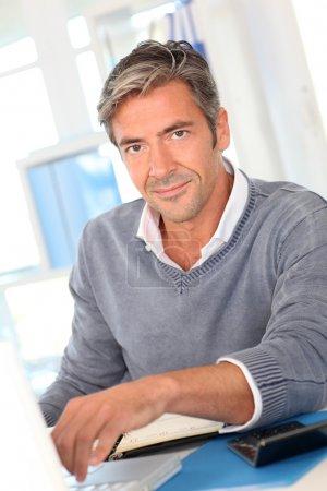 Photo pour Homme assis dans le bureau en face de l'ordinateur portable - image libre de droit