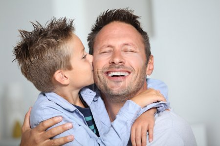 Photo for Little bond boy giving a kiss to his dad - Royalty Free Image