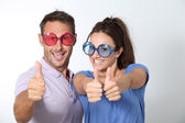 Couple wearing colored glasses having fun