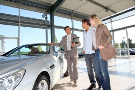 Car seller with couple in car dealership