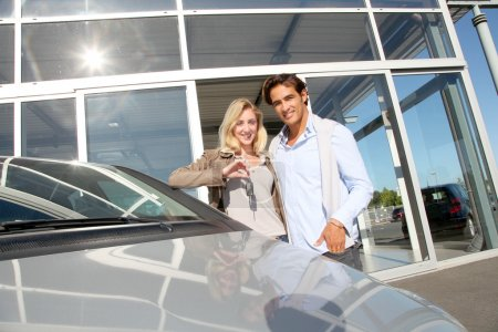 Couple holding car key in automobile dealership