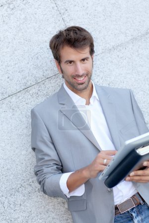 Handsome man leaning on wall with electronic tablet