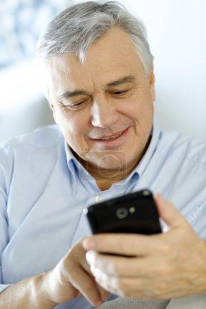 Portrait of senior man using smartphone