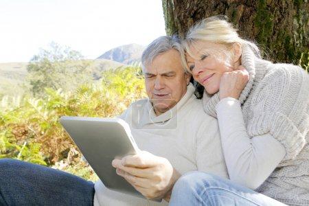 Photo pour Couple de personnes âgées à l'aide de la tablette en forêt - image libre de droit