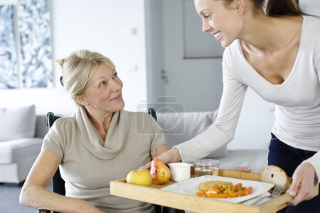 Young woman helping senior woman at home