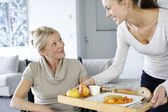 Mladá žena pomáhá starší žena v domácnosti