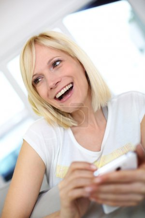 Photo for Smiling young woman at home using smartphone - Royalty Free Image