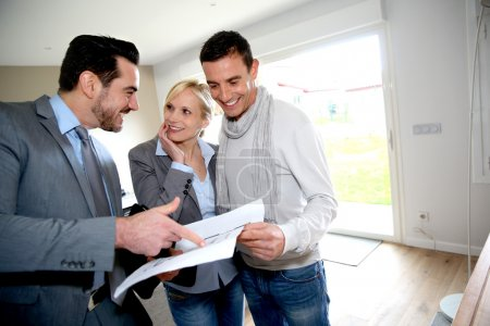Photo for Middle-aged couple visiting house with salesman - Royalty Free Image