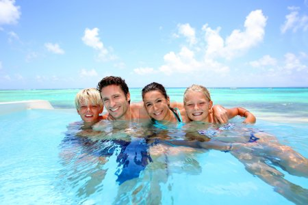 Photo for Family of four bathing in swimming pool - Royalty Free Image