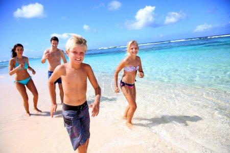 Family running on a paradisaical beach