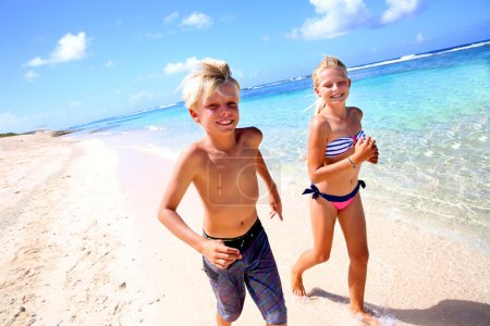 Kids running on a sandy beach in Caribe