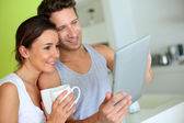 Cheerful couple using tablet at breakfast time