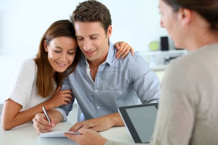 Photo pour Couple signant un contrat immobilier - image libre de droit