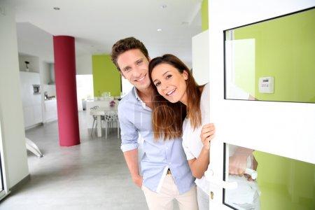 Fröhliches Paar lädt zum Betreten des Hauses ein