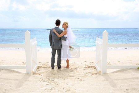 Photo pour Vient de se marier debout de couple par une clôture vers cet océan - image libre de droit