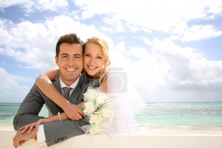 Just married couple leaning on fence by the beach