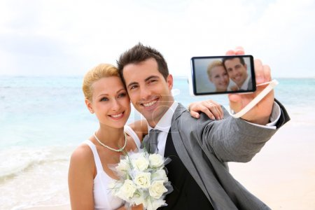 Photo for Bride and groom taking picture of themselves - Royalty Free Image