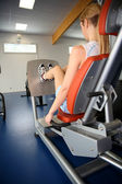 Woman exercising on legpress in gym center