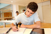 Portrait of student boy writing on notebook