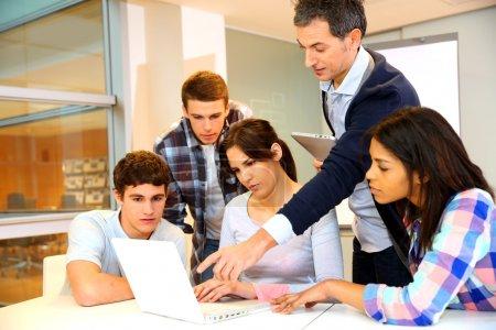 Photo pour Groupe d'étudiants en formation informatique avec professeur - image libre de droit