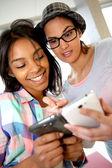 filles étudiant en utilisant le smartphone à l'école