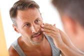 Muž v koupelně použití kosmetiky na obličeji