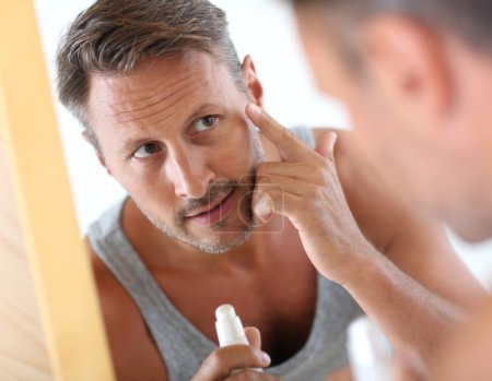 Photo for Man in bathroom applying cosmetics on his face - Royalty Free Image