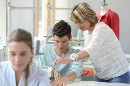 Photo pour Enseignant aidant étudiant avec machine à coudre - image libre de droit