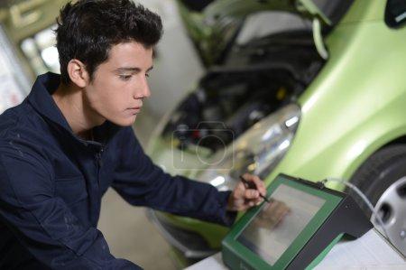 Photo pour Étudiants faisant diagnostic de voiture avec ordinateur - image libre de droit
