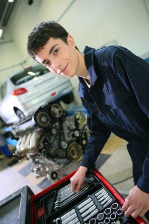 Photo pour Étudiant en mécanique travaillant sur le moteur de voiture - image libre de droit