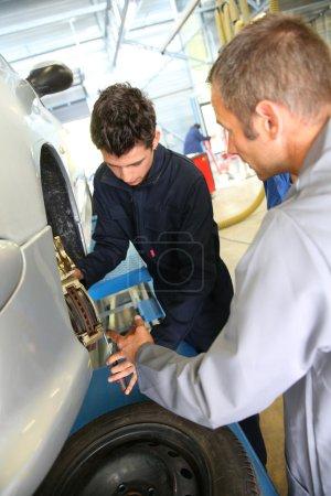 Photo pour Instructeur montrant à l'élève comment réparer la roue de voiture - image libre de droit