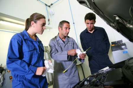 Instructor with students in repairshop changing motor oil