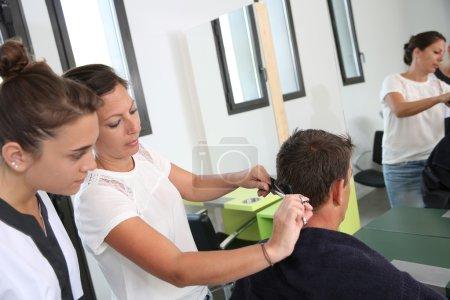 Photo pour Étudiante fille dans la coiffure apprendre à couper les cheveux - image libre de droit