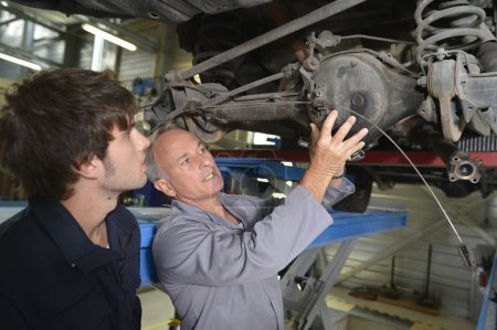 Teacher with student in car repairshop