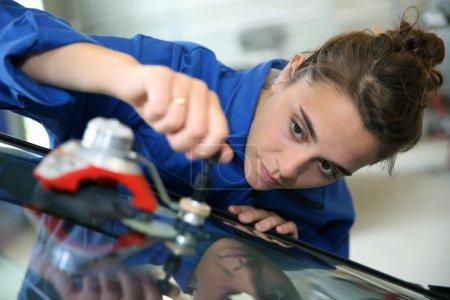 Photo pour Jeune étudiant en carrosserie changer pare-brise de voiture - image libre de droit