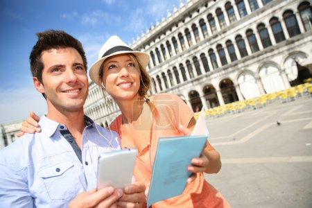 Photo for Couple in Venice looking at tourist information on smartphone - Royalty Free Image