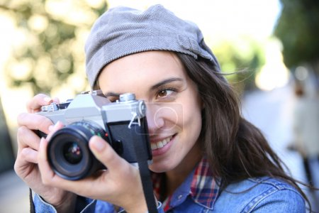Trendy girl holding camera