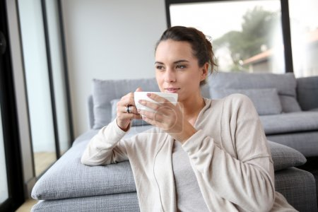 Photo for Peaceful woman relaxing at home with cup of tea - Royalty Free Image