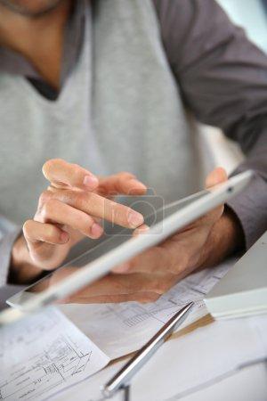 Man's hand using digital tablet
