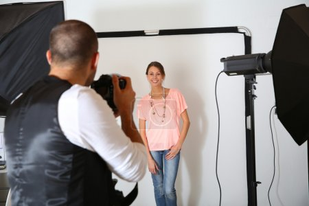 Photographer shooting model in studio