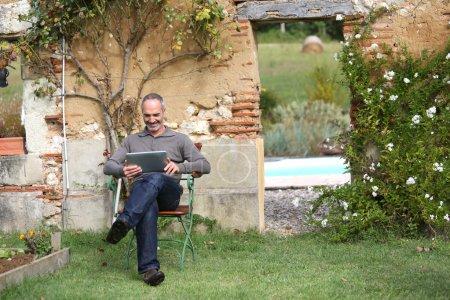 Photo pour Homme âgé relaxant avec tablette dans un jardin privé - image libre de droit