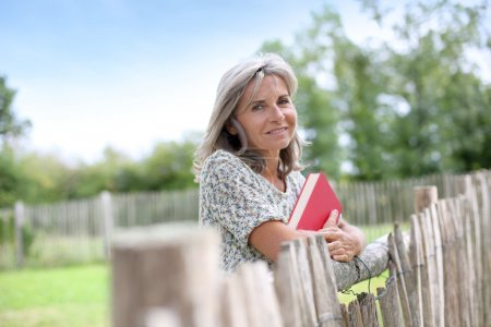 Woman standing by fence with book