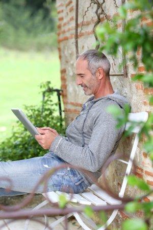 Foto de Hombre maduro utilizando tablet en un banco de campo - Imagen libre de derechos