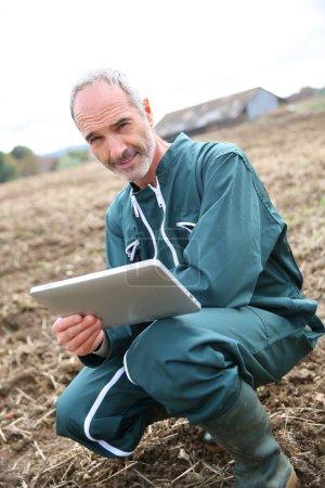 Farmer in field using digital tablet
