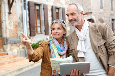Photo for Senior couple visiting city with map and tablet - Royalty Free Image
