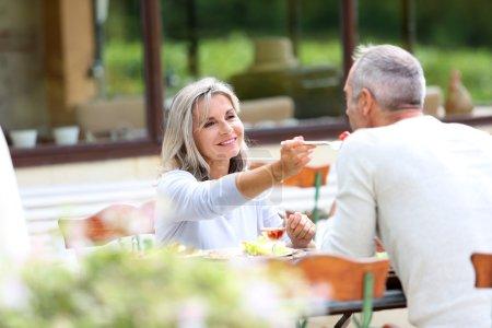 Photo pour Personnes âgées déjeunant dans le jardin - image libre de droit