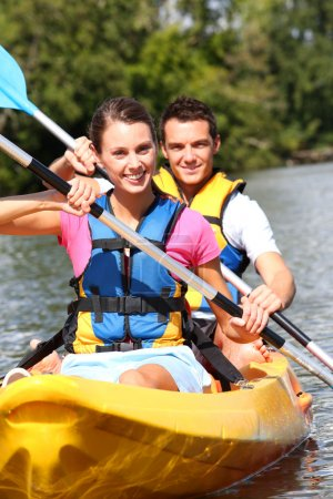 Photo for Couple riding canoe in river - Royalty Free Image