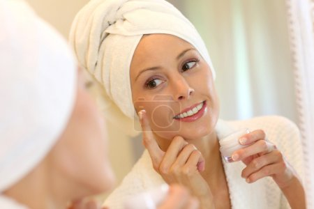 Woman applying skin lotion