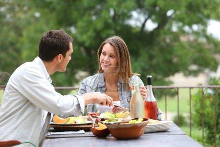 Photo pour Joyeux couple en train de déjeuner dans le jardin de l'hôtel - image libre de droit